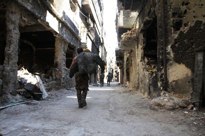 Des hommes passent devant des bâtiments détruits dans le camp de réfugiés palestiniens de Yarmouk, dans la capitale syrienne Damas, le 6 avril 2015.