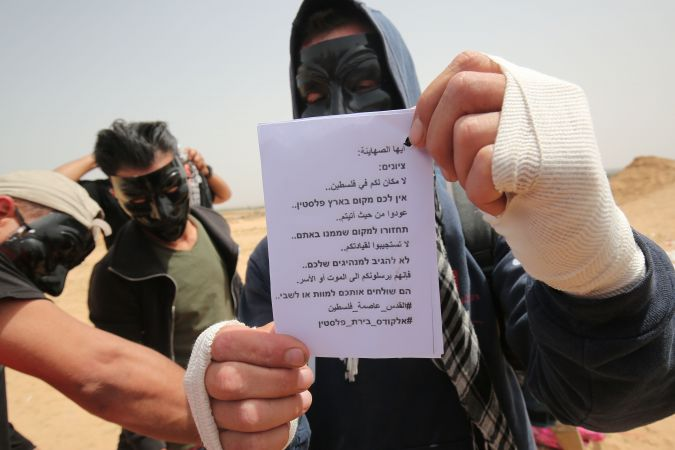 Palestinians show leaflets that will be attached to a kite before trying to fly it over the border fence with Israel, in Rafah in southern Gaza Strip on April 20, 2018. The message on the leaflet reads in Hebrew and in Arabic: 'Zionists: There is no place for you in Palestine. Go back to where you came from.'