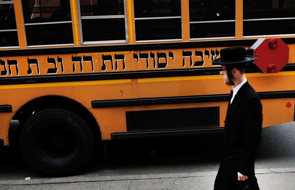 A young man walks by a school bus for a Hasidic yeshiva in Brooklyn.
